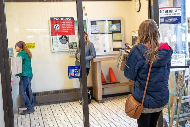 A woman carries her package and mail through the Snowmass Post Office on Feb. 15.