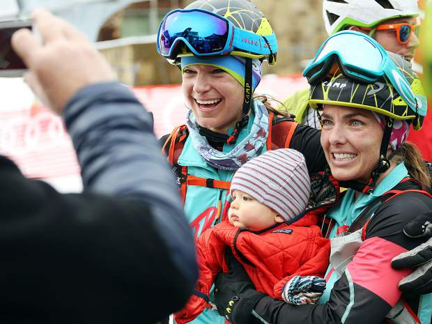 Jessie Young, right, holds her son, Ryder, while posing for a photo next to teammate Nikki LaRochelle after winning the 2019 Audi Power of Four ski mountaineering women's race on Saturday, March 2, 2019, in Aspen. (Photo by Austin Colbert/The Aspen Times).