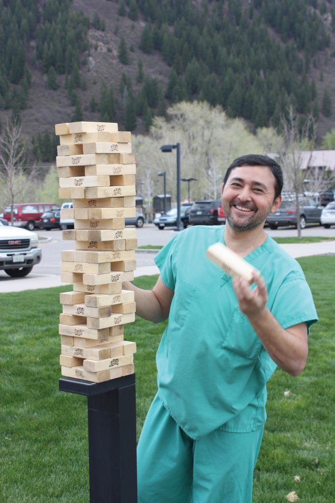 Victor Argueta from Environmental Services plays Jenga on the lawn.
