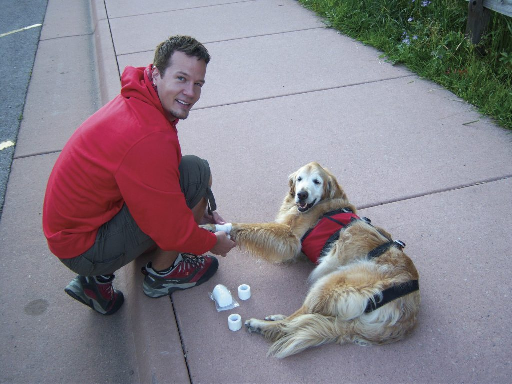Joshua Aho wraps Sawyer's ankles and wrists with gauze rolls and athletic tape in the Maroon Bells parking area before putting his shoes on for their hike. This was the routine before each hike and climb.