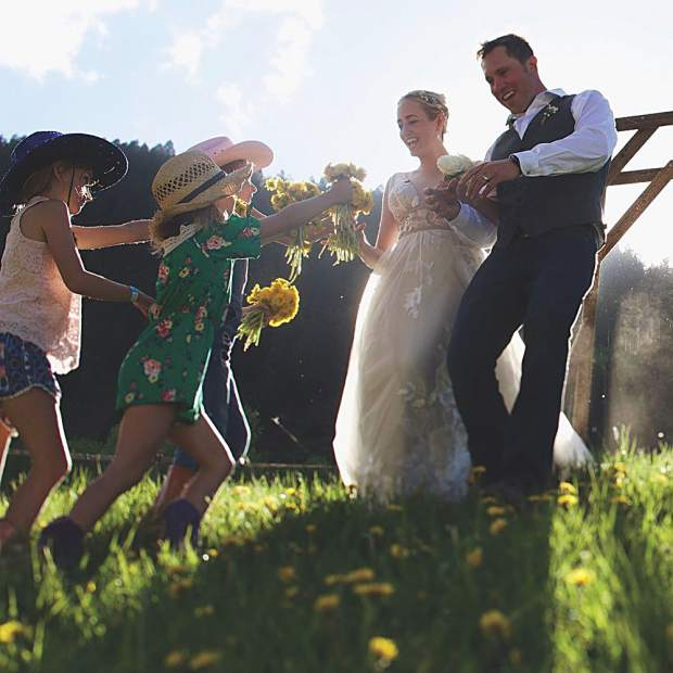 The newlyweds: Besha Deane and Ryan Jervis presented with freshly-picked dandelions from kids at their surprise wedding. Courtesy photo.