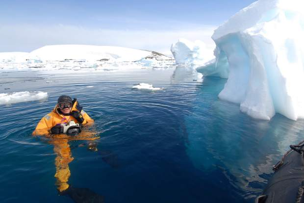 Photographer and filmmaker Pete McBride surfaces and tries to smile through numb lips while diving in Antarctica.
