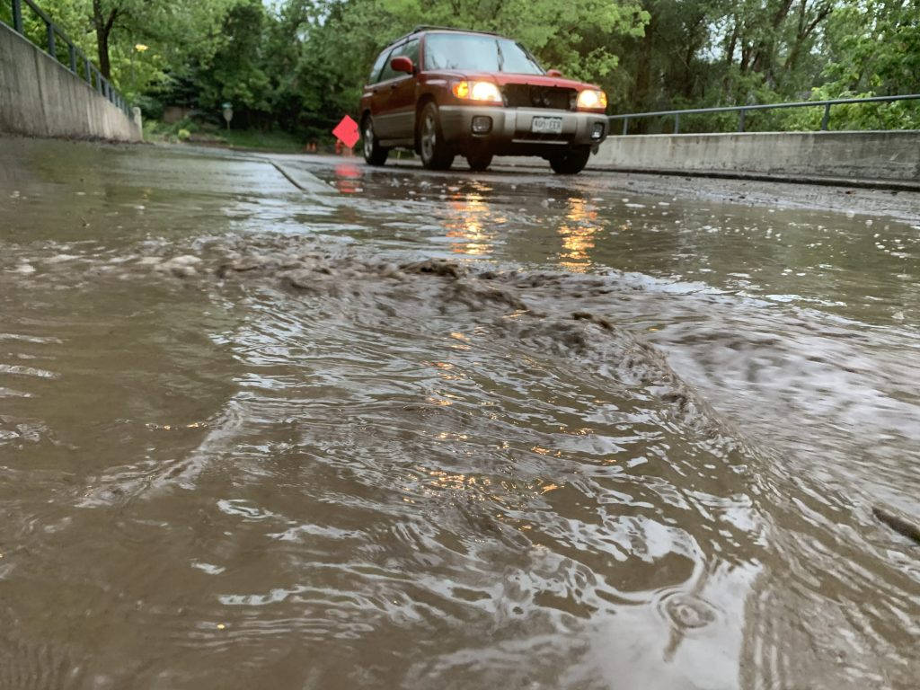 A car makes its way down Riverside Drive on Sunday after flooding around Basalt.