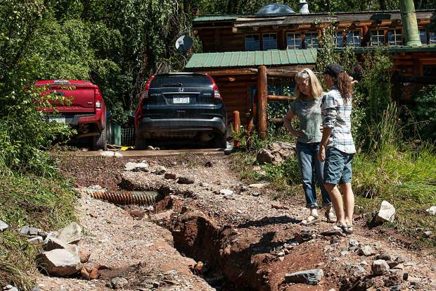 Debbie Redmount, left, speaks with a neighbor after assessing her and husband Sean Kelly's home damage on Cedar Drive on Monday as a result from the flash flooding rainstorm Sunday night.