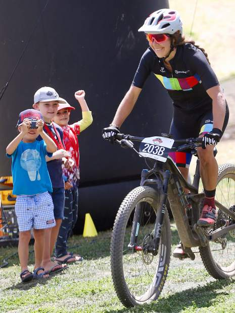 Aspen's Tess Strokes crosses the finish line of the Audi Power of Four mountain bike race on Saturday, Aug. 17, 2019 in Snowmass. Strokes, alongside husband Greg Strokes, won the 50-mile team event. (Photo by Austin Colbert/The Aspen Times)