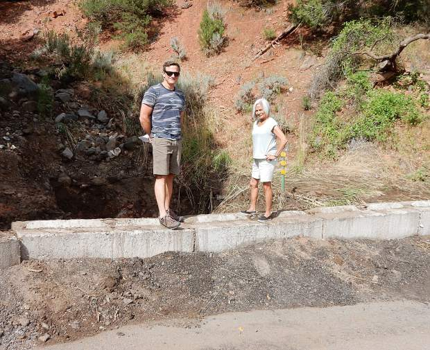 Keith McDougal and Geri Wright stand on a barrier at the intersection of Cedar Drive and Pinon in Basalt on Sunday. Water from the Lake Christine Fire burn scar overwhelmed a culvert at that site and swamped the neighborhood.