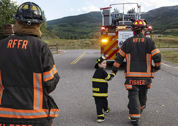 Wallace Fisher, 5, center, holds the hand of his dad, Roaring Fork Fire Rescue Lieutenant Andy Fisher, right, as they start the Axes and Arms 9/11 climb in Snowmass on Wednesday, September 11, 2019. (Kelsey Brunner/The Aspen Times)