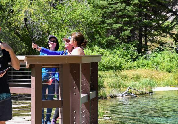 People stand together to take a selfie with Hanging Lake in the background.